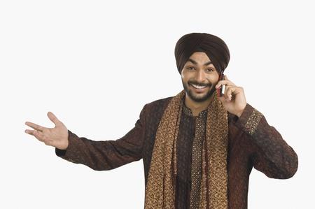 sikhism: Sikh man talking on a mobile phone and gesturing LANG_EVOIMAGES