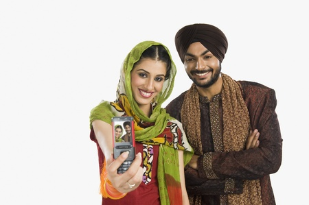 Sikh couple taking a picture of themselves with a mobile phone Stock Photo - 10166419