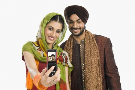 tradition: Sikh couple taking a picture of themselves with a mobile phone
