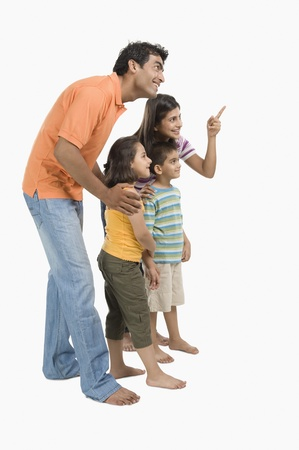 indian subcontinent ethnicity: Parents standing with their children and pointing