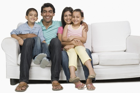 indian subcontinent ethnicity: Portrait of a family sitting on a couch and smiling