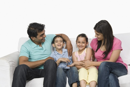 indian subcontinent ethnicity: Close-up of a family sitting on a couch and smiling