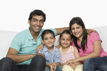 indian subcontinent ethnicity: Portrait of a happy family sitting on a couch