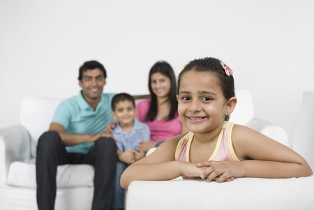 indian subcontinent ethnicity: Portrait of a girl smiling with her family in the background