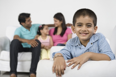 indian subcontinent ethnicity: Portrait of a boy smiling with his family in the background