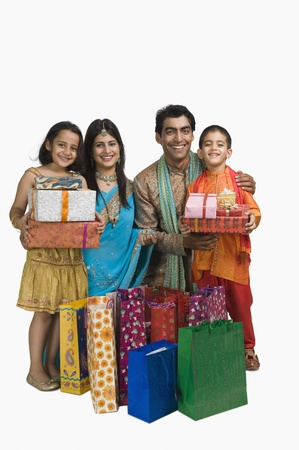 indian subcontinent ethnicity: Family holding shopping bags and gifts for Diwali LANG_EVOIMAGES