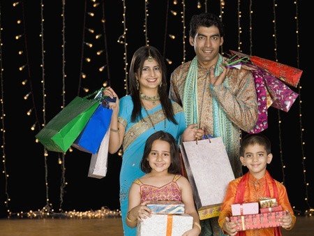 indian subcontinent ethnicity: Family carrying shopping bags and gifts for Diwali