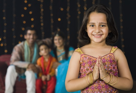 indian subcontinent ethnicity: Girl greeting on Diwali festival with her family in the background LANG_EVOIMAGES
