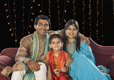 indian subcontinent ethnicity: Family sitting on couch and celebrating Diwali festival