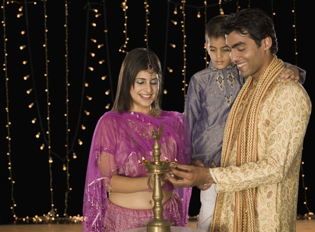 indian subcontinent ethnicity: Family lighting oil lamp on Diwali festival