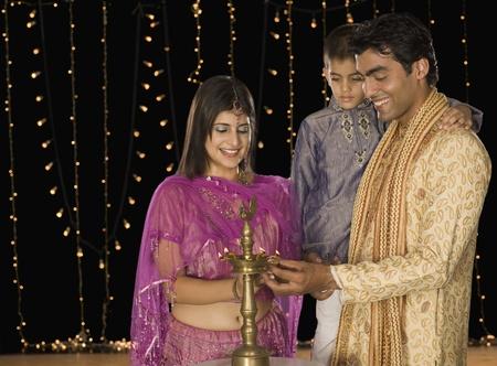 Family lighting oil lamp on Diwali festival