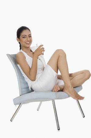 椅子およびガラスから水を飲んで座っている女性 写真素材