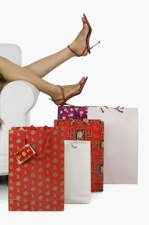 Low section of a woman on a couch surrounded by shopping bags Stock Photo - 10125405