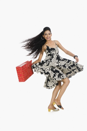 Woman carrying a shopping bag and dancing Stock Photo - 10125691
