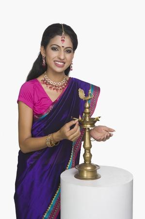 oil lamp: Woman lighting oil lamp LANG_EVOIMAGES