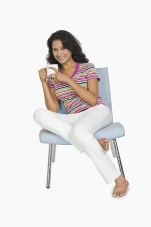 女性の椅子に座って、お茶を飲む