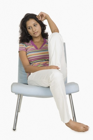 uncomfortable: Woman sitting on a chair and looking serious LANG_EVOIMAGES