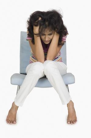 Donna seduta su una sedia e guardando depresso Archivio Fotografico - 10124123
