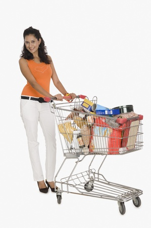 full shopping cart: Portrait of a woman pushing a shopping cart LANG_EVOIMAGES