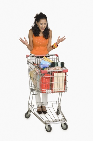 woman shopping cart: Woman looking at a shopping cart and surprised LANG_EVOIMAGES