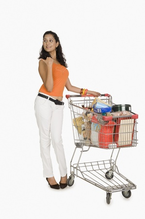 top: Woman standing with a shopping cart and pointing