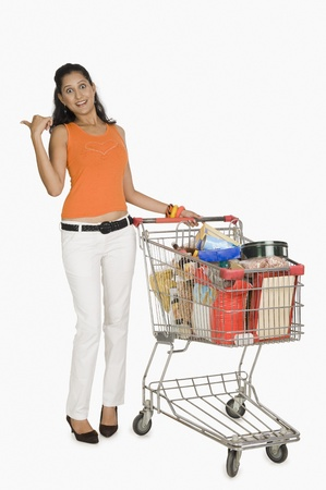 woman shopping cart: Woman standing with a shopping cart and pointing