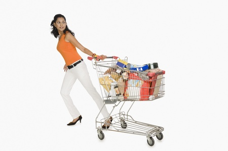 Woman pulling a shopping cart and smiling Фото со стока