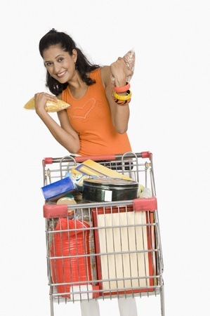 Woman standing with a shopping cart and smiling Stock Photo