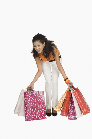 Woman trying to lift shopping bags Stock Photo - 10124288