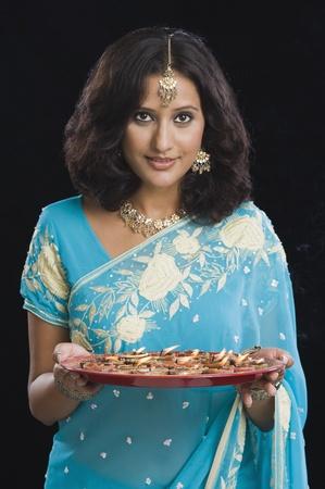 hinduismo: Mujer sosteniendo una tradicional thali de Diwali y sonriente