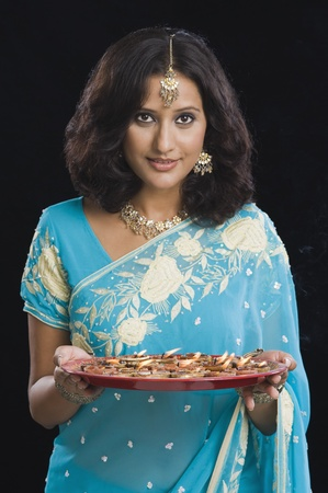 hinduism: Woman holding a traditional Diwali thali and smiling LANG_EVOIMAGES