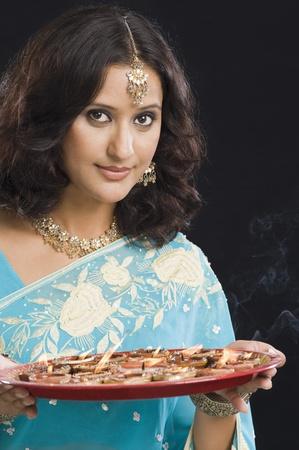 Vrouw die een traditionele Diwali thali en glimlachend