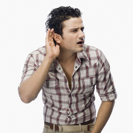 ear checked: Man trying to listen with a cupped hand on his ear LANG_EVOIMAGES