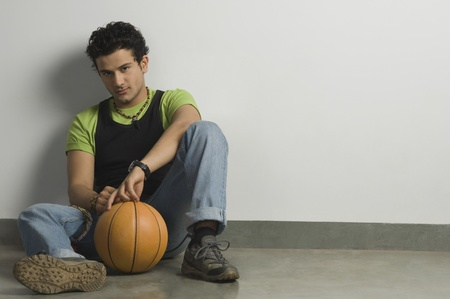 Portrait of a man sitting with a basketball Stock Photo - 10124791
