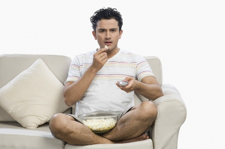 couches: Man watching television and looking surprised