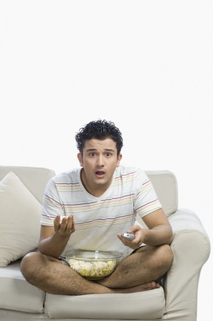 couch potato: Man watching television and looking surprised