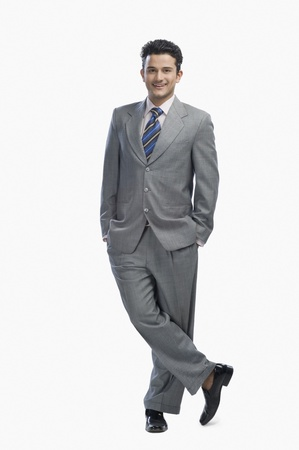 legs crossed at knee: Portrait of a businessman smiling LANG_EVOIMAGES