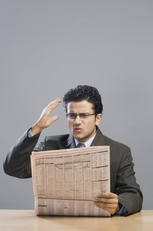 financial newspaper: Businessman reading a financial newspaper and looking disappointed