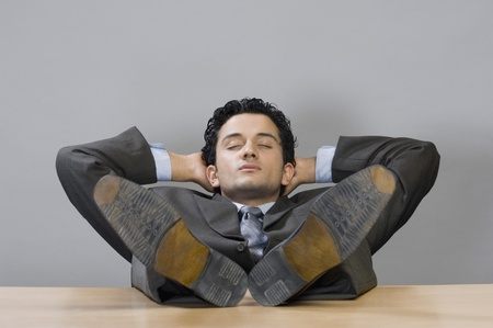 Businessman napping with his feet on desk