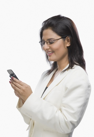clipping  messaging: Businesswoman text messaging on a mobile phone LANG_EVOIMAGES