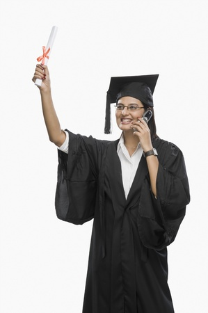 Graduate woman talking on a mobile phone and holding her diploma Stock Photo - 10125783