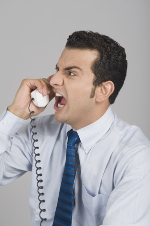 Businessman shouting over a telephone