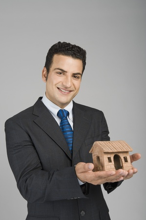 Businessman holding a model home Stock Photo - 10169418