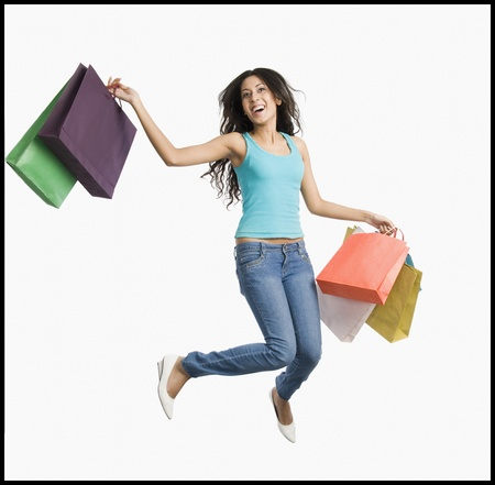 retail therapy: Woman carrying shopping bags and jumping on a trampoline
