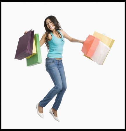 Woman carrying shopping bags and jumping on a trampoline Stock Photo - 10123963