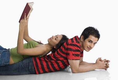 Vrouw liggend op de rug van een man en een boek te lezen Stockfoto