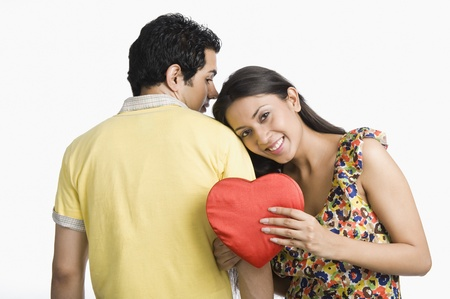 Woman leaning on a mans shoulder and holding a present Imagens
