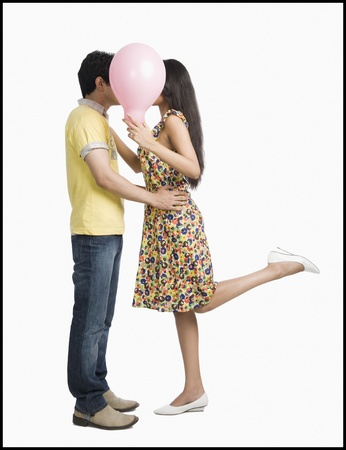Couple kissing behind a balloon