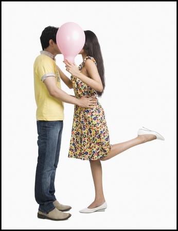 Paar kussen achter een ballon