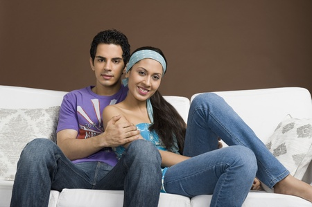 couple on couch: Couple sitting on a couch with arm around